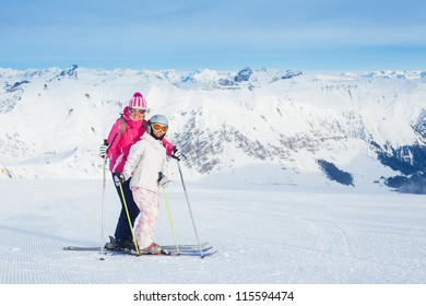 Happy smiling woman in ski goggles and with her daughter, Zellertal, Austria