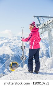 Happy smiling woman in ski goggles against a ski-lift and wonderful winter mountains backgroundagainst wonderful winter mountains background and , Zellertal, Austria