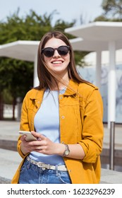 Happy smiling woman with smartphone in hands. Cute woman in sunglasses, street fashion look, casual outfit.