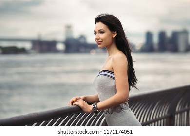 Happy smiling woman standing on ocean pier in New York City and looking to the side