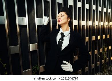 happy smiling woman stewardess in uniform posing near an unusual wall, waiting for her flight