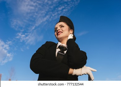 happy smiling woman stewardess in uniform waiting for flight, against blue sky background