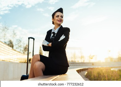 happy smiling woman stewardess in uniform with suitcase waiting for her flight