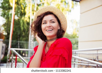 Happy smiling woman in straw hat and bright red dress on the street. Beautiful woman with black eyes and dark curly hair. Summer outfit