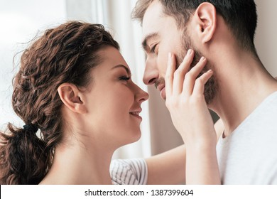 happy smiling woman stroking bearded boyfriend at home
