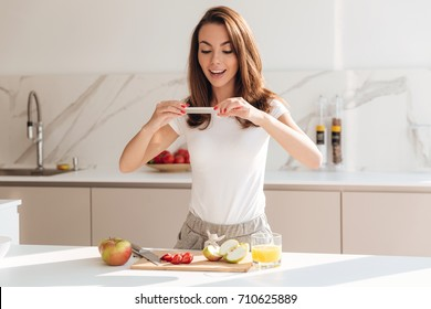 Happy smiling woman taking a picture of fruit slices on a wooden board with mobile phone while standing at the kitchen