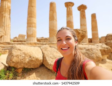 Happy smiling woman taking self portrait with greek temple on the background in the Valley of the Temples at Agrigento, Italy