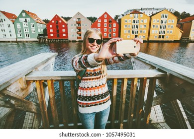Happy smiling woman taking selfie  traveling in Trondheim city Norway vacations weekend Lifestyle fashion outdoor scandinavian houses landmarks architecture on background