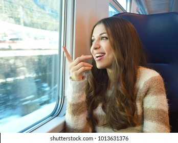 Happy smiling woman travelling in train and pointing a place through the window