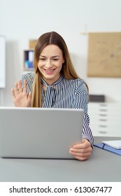 Happy smiling woman waving at her laptop computer as she interacts on a video conferencing call while sitting in an office