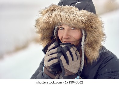 Happy smiling woman wearing a fur trimmed hooded jacket enjoying a mug of coffee cradled in her gloved hands outdoors in winter snow in a concept of the seasons in a close up portrait
