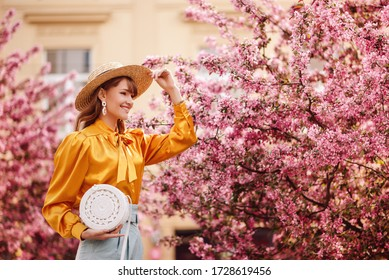 Happy smiling woman wearing trendy wide brim straw hat, yellow vintage blouse, holding round wicker rotang bag, posing, walking in street near pink spring blossom trees. Copy, empty space for text