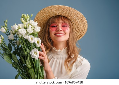 Happy smiling woman wearing trendy spring outfit: pink sunglasses, straw hat, holding flowers, posing on blue background. Copy, empty space for text