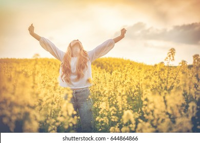 Happy smiling woman in yellow rapeseed field at sunset, freedom concept