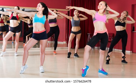 Happy smiling women are dancing modern jazz in gym.