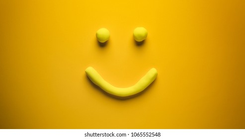 Happy and smiling - a yellow emoticon make out of modelling clay on a yellow background.