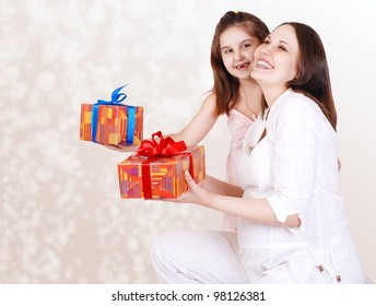 Happy smiling yong pregnant mother with little daughter and gift boxes