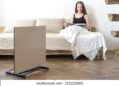 Happy and smiling young adult woman sitting on sofa and reading book in warm home with heater. Selective focus of electric radiator in cozy house with copy space in modern interior room