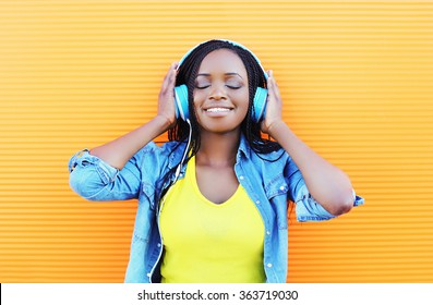 Happy smiling young african woman with headphones enjoying listens to music over orange background