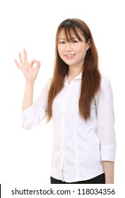 Happy smiling young asian business woman with okay gesture