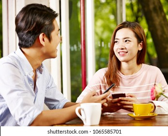 happy and smiling young asian couple talking while playing with mobile phone in coffee shop or tea house.