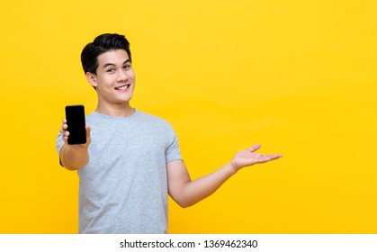 Happy smiling young Asian man showing mobile phone with another hand open on colorful yellow background
