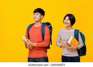 Happy smiling young asian students carrying books to school in yellow isolated studio background