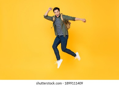 Happy smiling young Asian tourist man with backpack jumping in mid-air isolated on yellow background