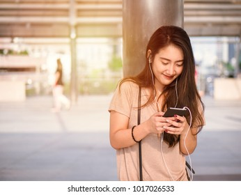 Happy smiling young asian woman listens to music in headphone and using smartphone searching for social media.