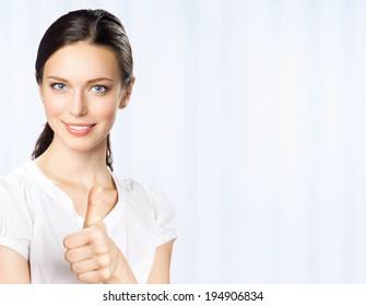 Happy smiling young beautiful business woman showing thumbs up gesture, at office, with copyspace