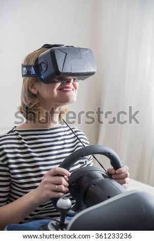 3827d20a18a happy smiling young beautiful girl holding a gaming computer wheel getting  experience using VR-headset glasses of virtual reality at home - Image