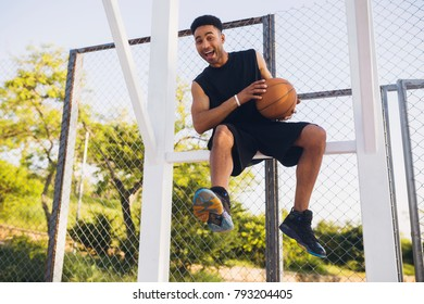 happy smiling young black man sitting on court, basketball game player, having fun, holding ball, funny, resting, positive face expression, emotional