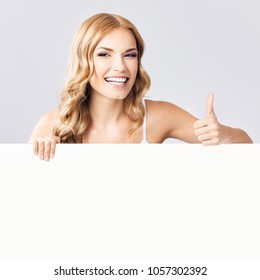 Happy smiling young blond woman showing blank signboard or empty copyspace area for slogan or advertising text, with thumbs up gesture, over grey background