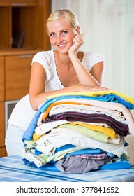 Happy smiling young blonde woman sorting out laundry at home