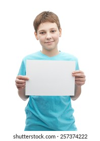 Happy smiling young boy in a cyan t-shirt with a empty copyspace A4 sheet of paper in front of him, composition isolated over the white background