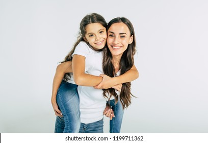 Happy smiling young brunette mother holds on back her cute little daughter in white T-shirts isolated in studio