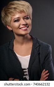 Happy smiling young business blond woman with short bob hair style looking in grey trendy jacket on dark background