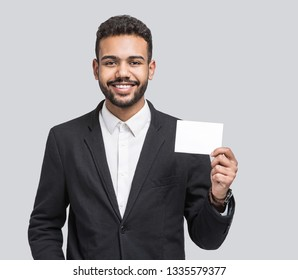 Happy smiling young business man showing blank card, isolated over gray background. Handsome man with white card