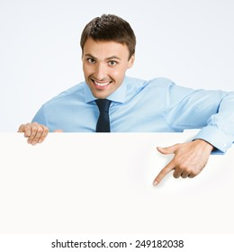 Happy smiling young business man showing blank signboard, over grey background, with copyspace area for text or slogan