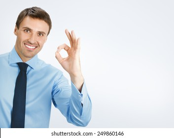 Happy smiling young business man with okay gesture, on grey background, with copyspace area for text or slogan