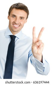 Happy smiling young business man showing two fingers or victory gesture, isolated on white background. Success in business, job and education concept shot.