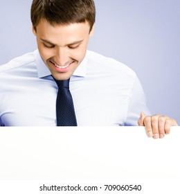 Happy smiling young business man showing blank signboard, against violet background