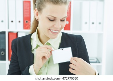 Happy smiling young business woman wearing blank badge. Name tag on chest. Person identity label. Business card mock-up.