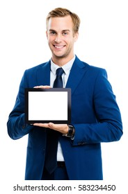 Happy smiling young businessman showing blank no-name tablet pc monitor, isolated over white background, with copyspace area for slogan or text message. Success in business concept studio shot.