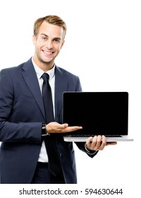 Happy smiling young businessman showing blank laptop monitor, isolated over white background, with copyspace area for slogan or text message. Success in business concept studio shot.