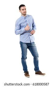 Happy smiling young businessman with thumbs up gesture looking at camera. Full body length portrait isolated over white background.