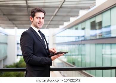 Happy smiling young businessman using his digital tablet at the office