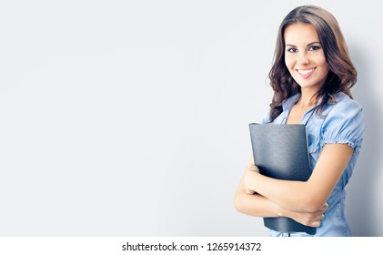 Happy smiling young businesswoman with black folder, against grey background, with blank copyspace place for advertising slogan or text. Caucasian brunette model in business concept studio shoot.