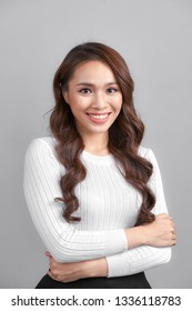 Happy smiling young businesswoman, on grey background. Blank copyspace area for advertise text or slogan.
