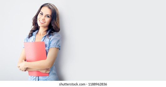 Happy smiling young businesswoman with red folder, against grey background, with blank copyspace place for advertising slogan or text. Caucasian brunette model in business concept studio shoot.